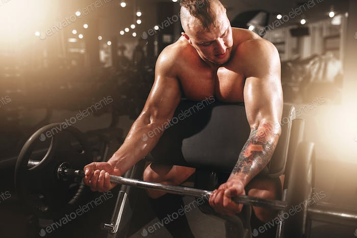 Strong athlete with muscular body lifting barbell