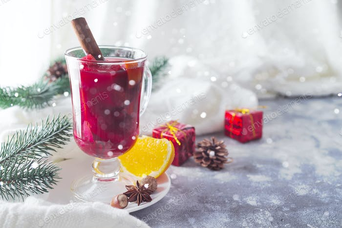 Hot red mulled wine with spices and a warm white plaid on a stone background