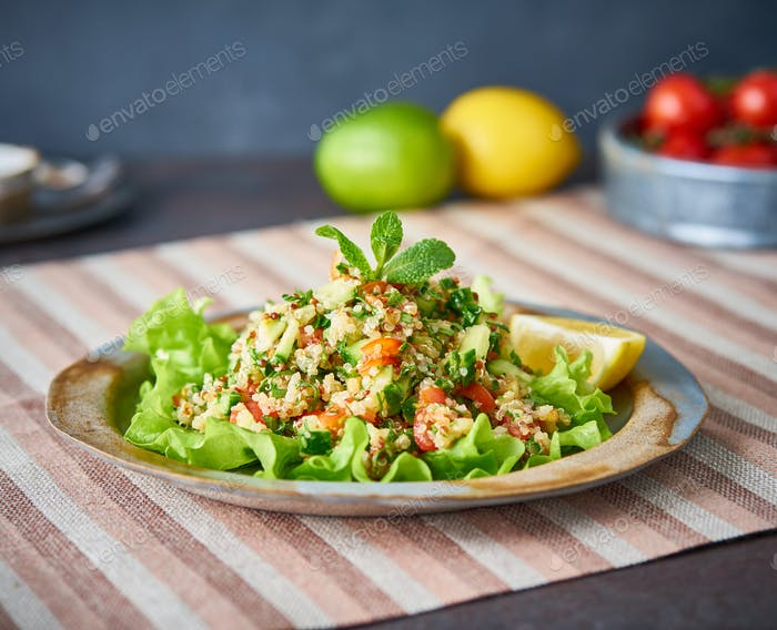 Tabbouleh salad with quinoa. Eastern food with vegetables mix, vegan diet. Side view,