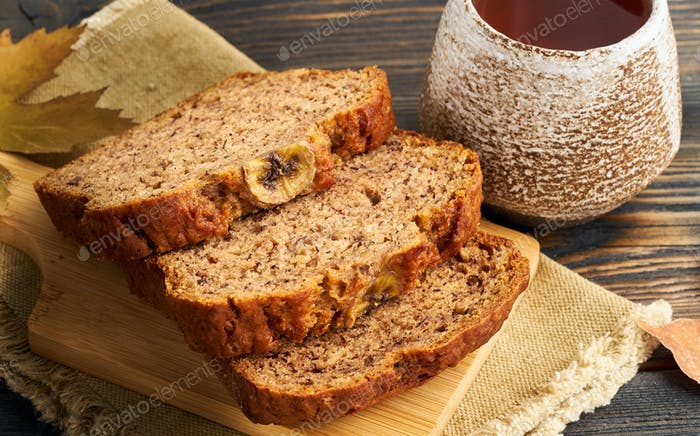 Autumn food-slices of banana bread, a Cup of tea, dry leaves, a dark wooden table. Side view.