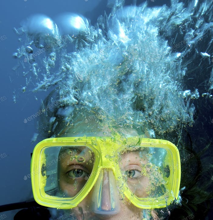 Close up of teenager's face while scuba diving.