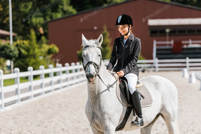 attractive smiling female equestrian riding horse at horse club