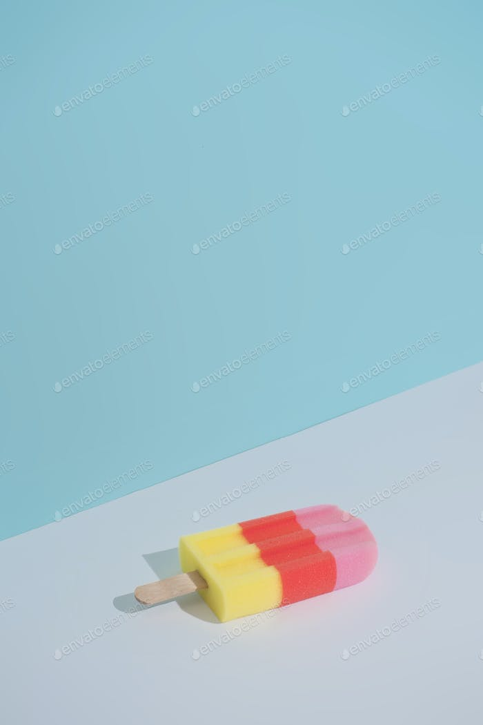 Colorful Ice cream popsicle on pastel blue background. Minimal summer composition.
