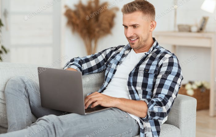 Happy freelancer chatting online on laptop at home