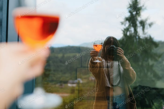 Woman holding aperol drink in hand and taking selfie in big window