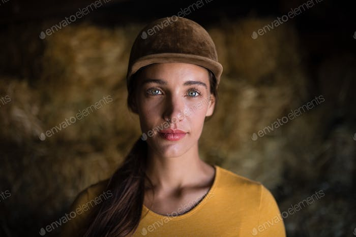 Portrait of serious female jockey in stable