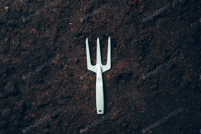 Rake for work in agriculture over soil background. Agriculture, organic gardening, planting or