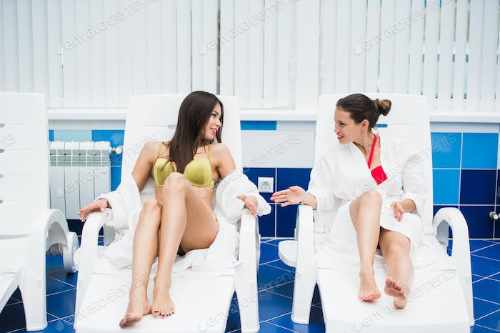 Two young women relaxing by the poolside wearing toweling robes