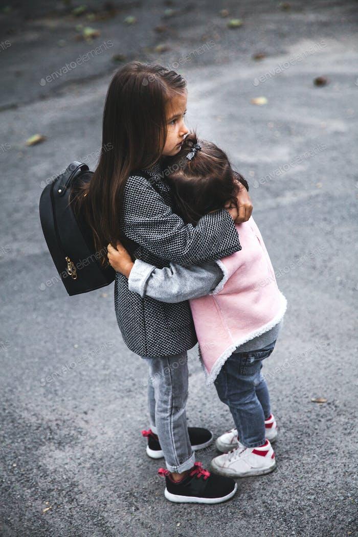 Little girls hug in the street. Stylishly dressed. Man, fashion, relationship, love