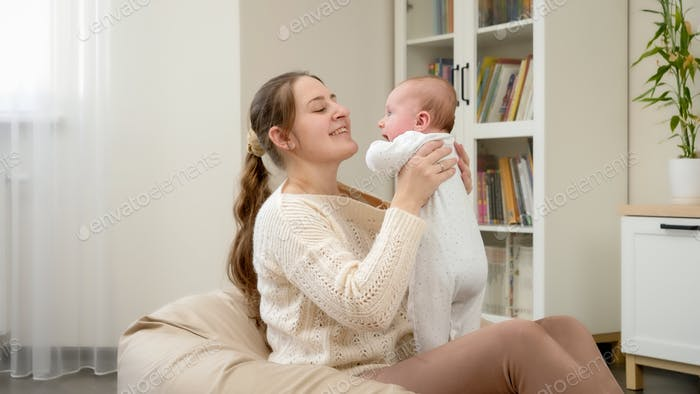 Smiling young mother sitting in beanbag and holding her little baby son. Parenting, children