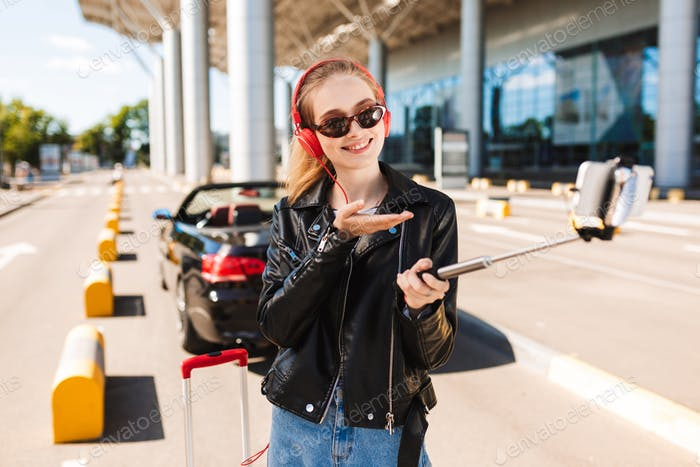 Joyful girl in sunglasses and headphones happily taking photo on