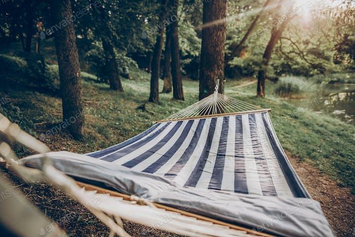 Stylish striped hammock hanging outdoors at nature resort close-up