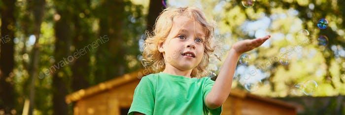 Pequeño niño jugando con las Burbujas de jabón