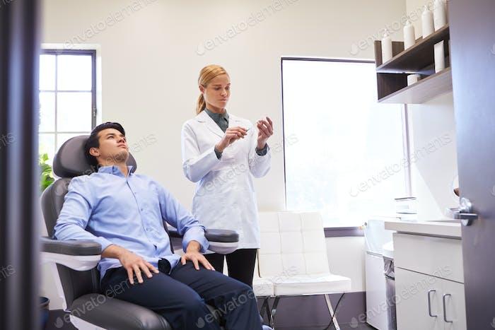 Mann sitzend in Stuhl sein geben botox Injektion durch weibliche Arzt