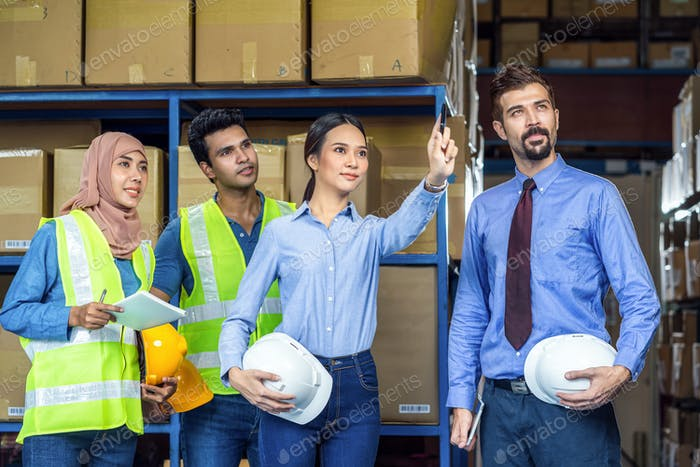 Group of Diversity warehouse worker checking and pointing to product when walking and meeting