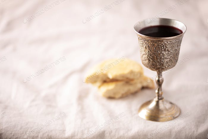 Unleavened bread, chalice of wine, silver kiddush wine cup on canva background. Communion still life