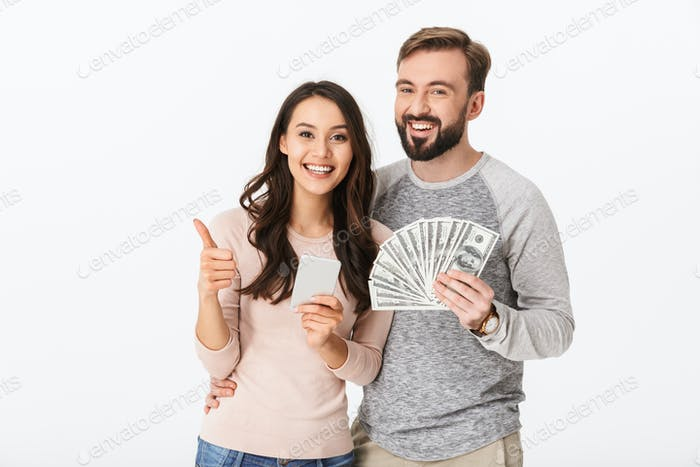 Happy young loving couple holding money showing thumbs up using mobile phone.