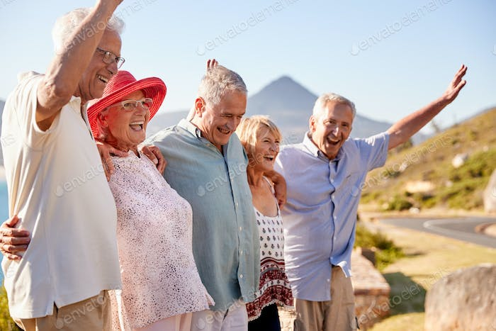 Senior Friends Visiting Tourist Landmark On Group Vacation With Arms Raised