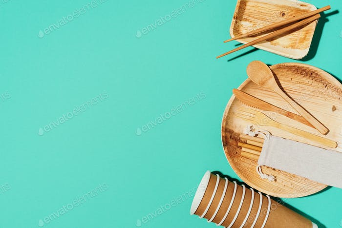 Bamboo plates, wooden spoon, fork, knife, craft paper cups on blue background. Disposable tableware