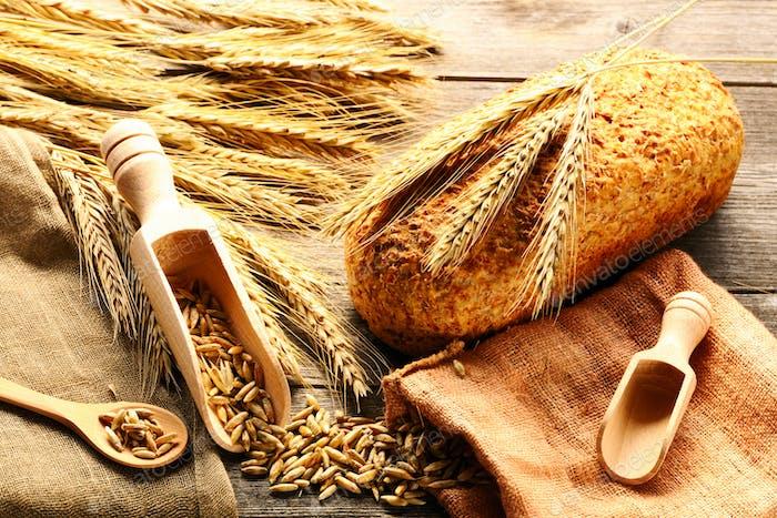 Roggen Ährchen und Brot Stillleben auf hölzernem Hintergrund
