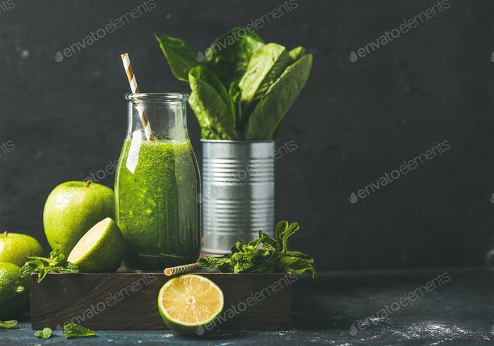 Green smoothie in glass bottle with fresh fruits, copy space