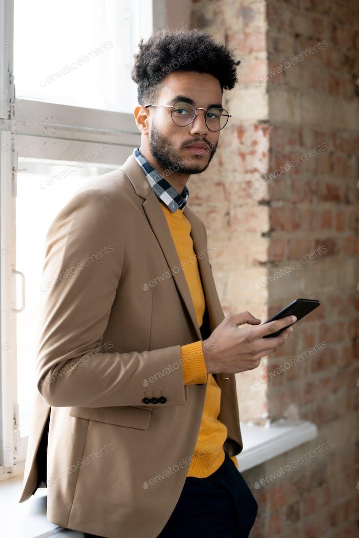 Confiado hombre de negocios de moda con gadget