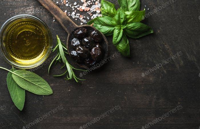Greek black olives, fresh herbs and oil on dark rustic wooden background.