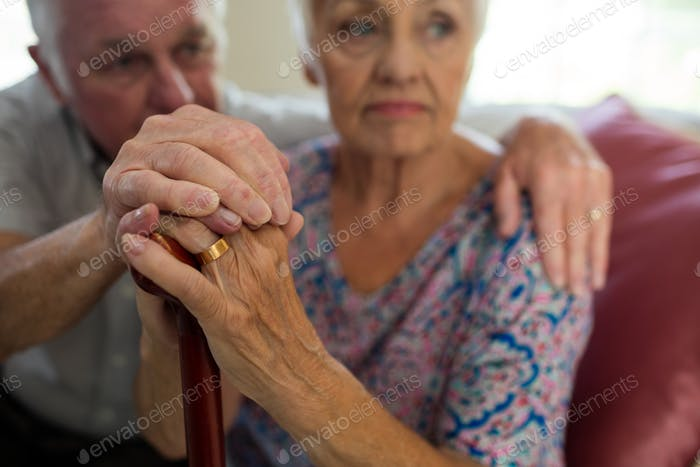 Senior man holding hands of old woman with walking stick in living room