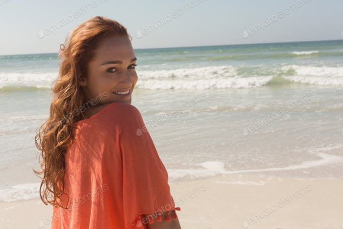 Side view of happy beautiful young Caucasian woman looking at camera on the beach.She is smiling