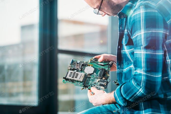 Инженер оборудования, работающий с печатной платой