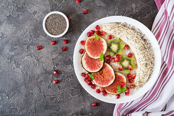 Delicious and healthy oatmeal with figs, kiwi, pomegranate, banana