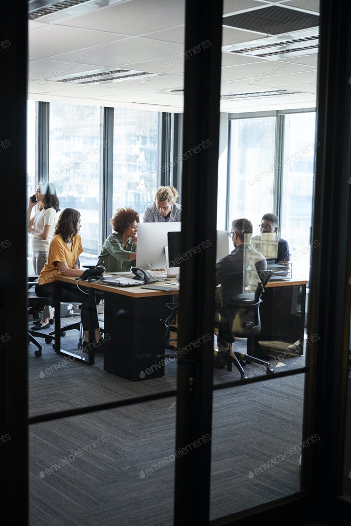 Creative business team working in a casual office, seen from doorway through glass wall, vertical