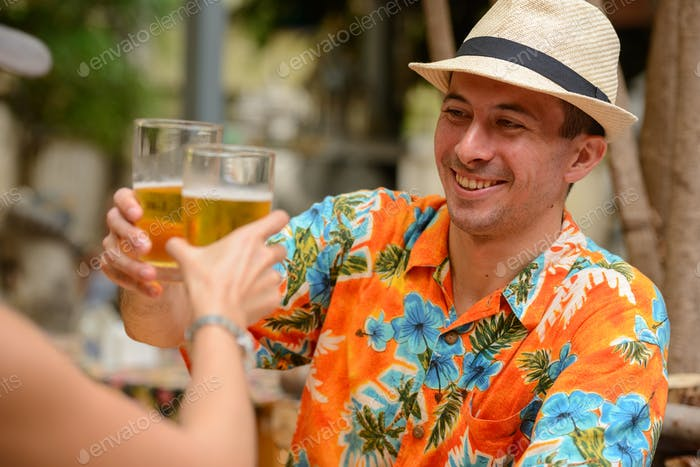 Happy multi ethnic tourist couple drinking beer together at restaurant