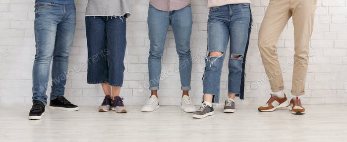 Legs of friends. Young people in jeans and trousers