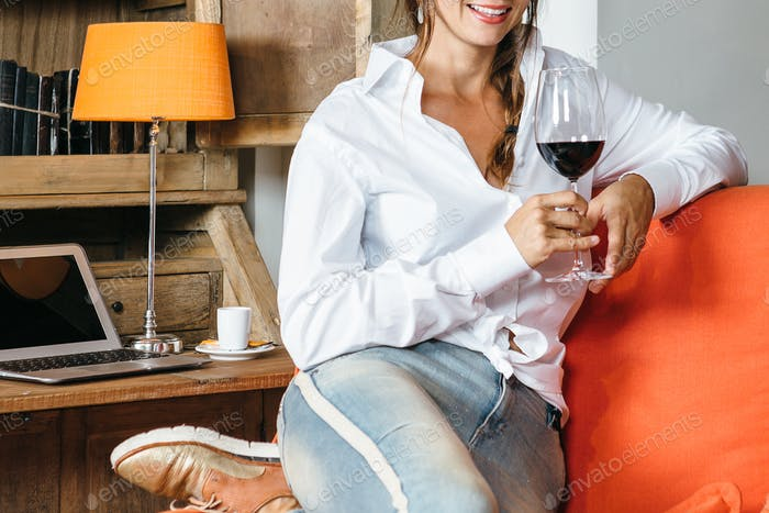 Young female with wineglass on sofa