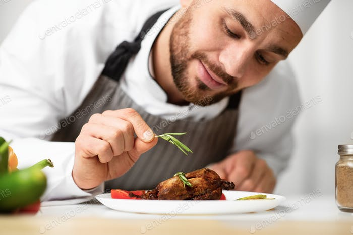 Male Chef Decorating Chicken Dish Cooking In Restaurant Kitchen, Cropped