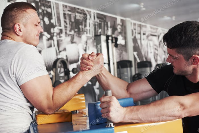 Struggles to win. Arm wrestling challenge between two men. Match on a special table