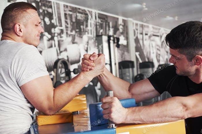 Kämpft um den Sieg. Armwrestling-Herausforderung zwischen zwei Männern. Spiel auf einem speziellen Tisch