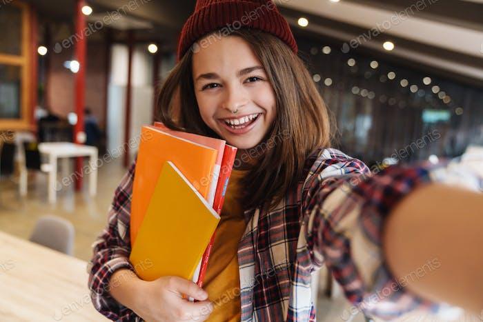 Bild von fröhlichen Mädchen nehmen selfie während halten Übungsbücher