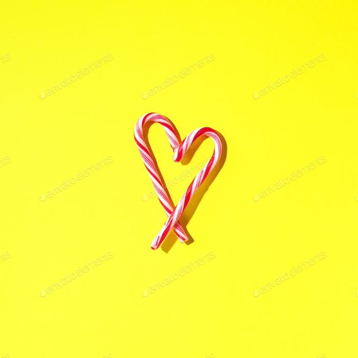Christmas candy cane heart on yellow background with copy space. Top view. Love, Valentines day