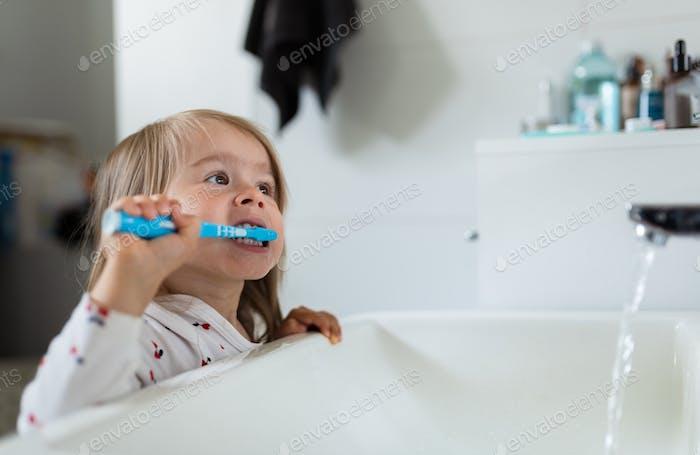 Baby-Mädchen in hellen Bad putzt ihre Zähne über der Spüle