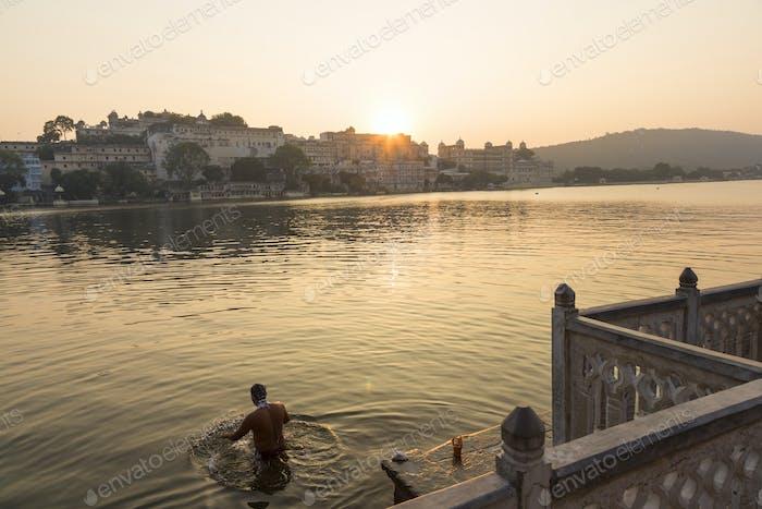 Menschen schwimmen in einem See am frühen Morgen.