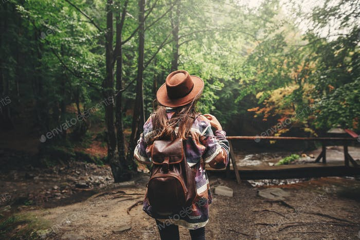 Stylish hipster girl in hat traveling in mountains