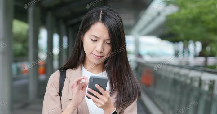Business woman work on smart phone in city