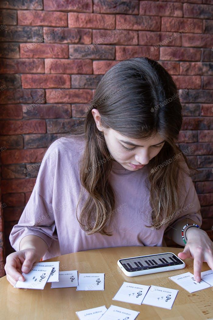 Das Mädchen studiert Noten und Musiktheorie mit Spezialkarten.