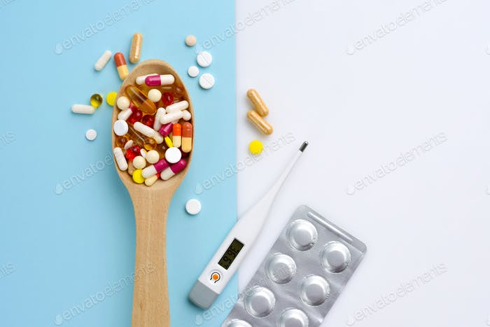 Wooden spoon full of pills, tablets, capsules and thermometer on blue background. Top view