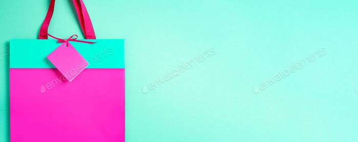Top view of turquoise and pink paper shopping bag on trendy green background. Copy space. Gift