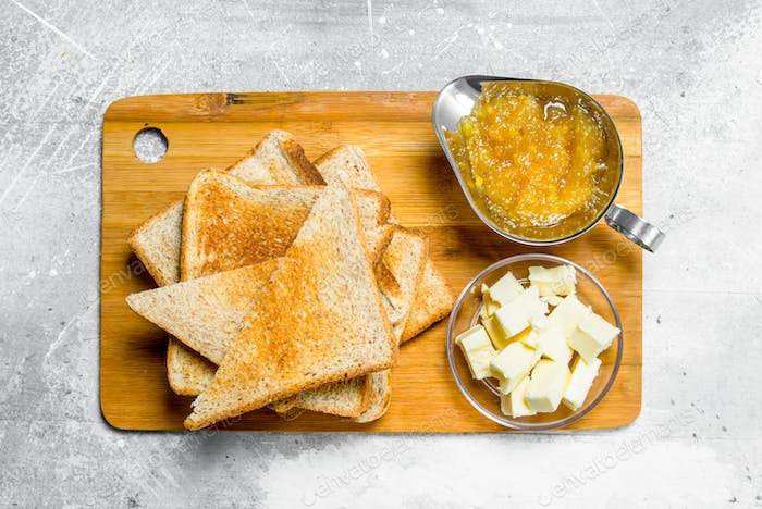 Breakfast. Toasted bread with butter and jam on a wooden Board.