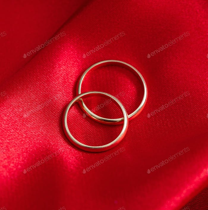 Two golden wedding rings on red satin background.