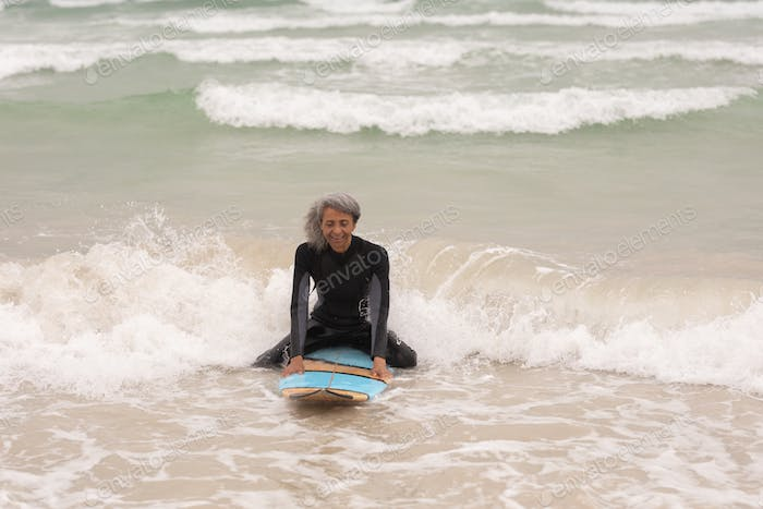 Front view of happy senior female surfer sitting on surfboard in sea